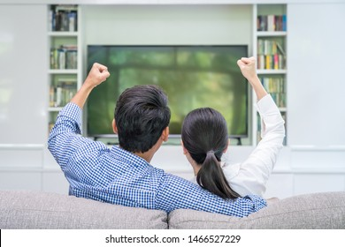 Happy young loving couple watch tv in the living room