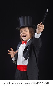 Happy young magician performing a trick with wide gestures - on dark background