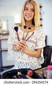 Happy young makeup artist holding brushes