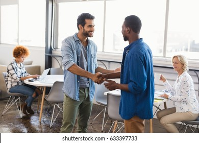 Happy young male business people shaking hands at creative office