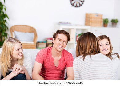 Happy young male and female friends spending time together at home