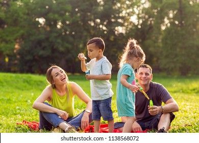 Happy young male and female playing with children outside