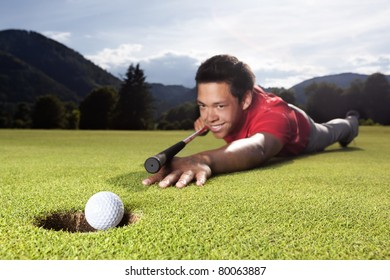 Happy young male golf player lying on green and using golf club as billiard cue (queue) to hole ball into cup.