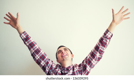 happy young male with his arms up in victory gesture