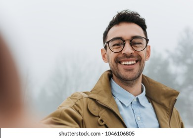 Happy young male is making self portrait on a camera outdoors. Handsome young man in coat and blue shirt wear eyeglasses making selfie and smiling while standing against grey misty nature background