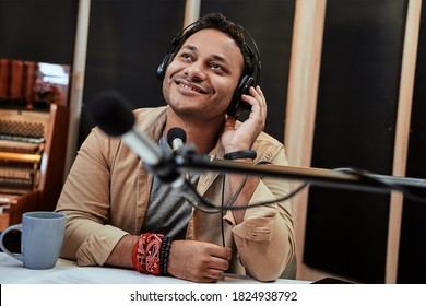 Happy young male radio host looking aside while broadcasting in studio, using microphone and headphones