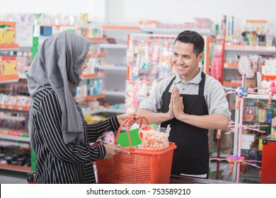 happy young male shopkeeper or cashier  welcoming customer at supermarket