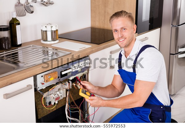 Happy Young Male Technician Checking Dishwasher With Digital Multimeter