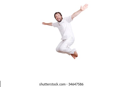 Happy young male in white clothes is jumping isolated
