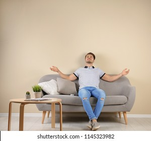 Happy young man with air conditioner remote at home