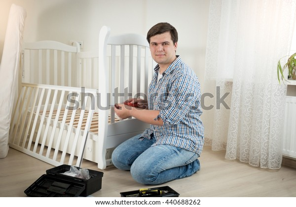 Happy young man assembling white wooden crib in nursery