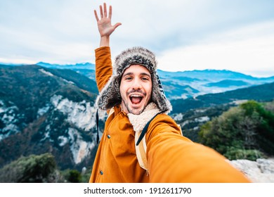 Happy young man with backpack is taking a selfie on the top of mountains - People, technology, sport and lifestyle concept.