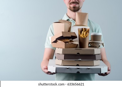 Happy young man with beard holding pizzas, hamburger in paper box, take-out coffee cups in holder and French fries, close-up. Light grey background. Fast food delivery.