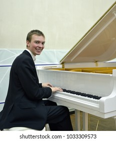 Happy young man behind white grand piano