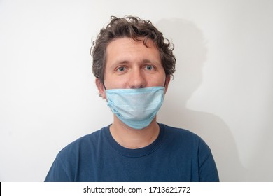 A happy young man is in a blue medical mask. Mask mode - wrong using a medical mask from infection.