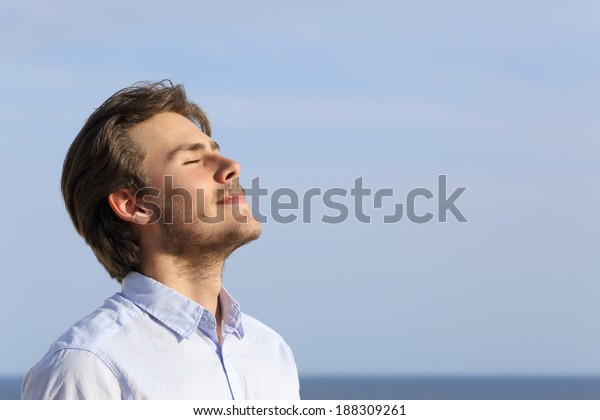 Happy young man breathing deep with the horizon in the background
