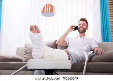 Happy Young Man With Broken Leg Sitting On Sofa Talking On Smartphone