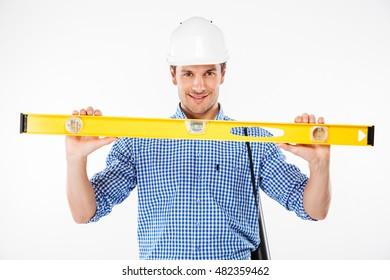 Happy young man builder in building helmet holding spirit level