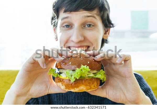 Happy young man with burger in hands