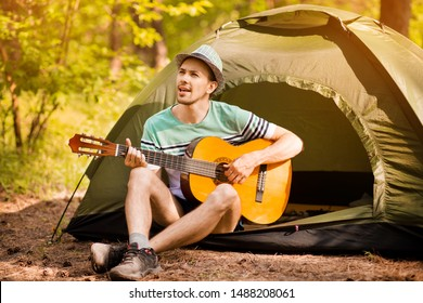 Happy young man camping and strum a guitar instrumental music to relax against background of forest sunset.