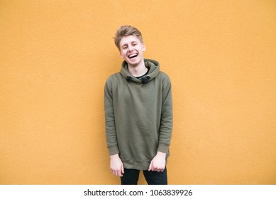Happy young man in casual clothes stands on the background of an orange wall and smiles. A smiling student on the background of a colored orange wall.