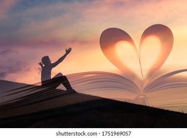 Happy young man celebrating success with a Bible heart shaped book against sunset sky. With his arms up praising God. Double exposure