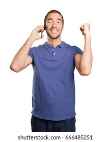 Happy young man celebrating and using a mobile phone on white background