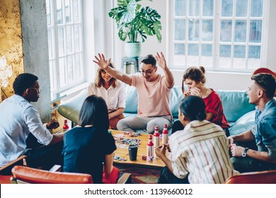 Happy young man with chips celebrating win playing game with best friends at table in modern apartment.Amazed hipster guy get victory in poker spending leisure time with multicultural young people