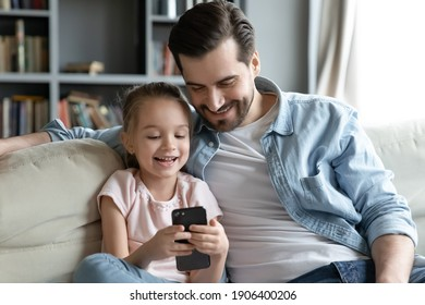Happy young man cuddling little 6s daughter, playing together on smartphone. Smiling small preschool girl enjoying using mobile applications or watching funny video sitting with caring daddy on sofa.