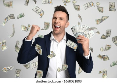 Happy young man with dollars under money rain on light background