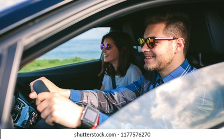 Happy young man driving a car accompanied by his girlfriend