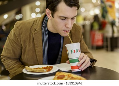 Happy Young Man Eating Pizza At The Food Court In A Mall