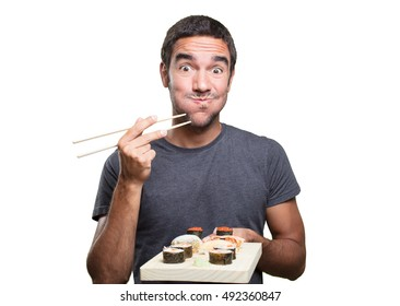Happy young man eating sushi