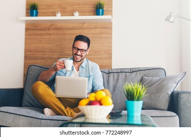Happy young man enjoying with coffee and laptop