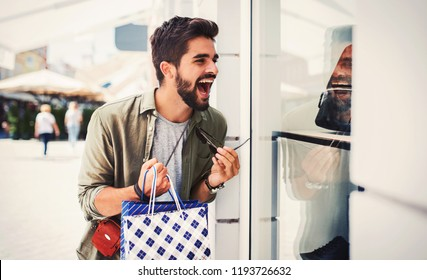 Happy young man enjoying in shopping. Consumerism, fashion, lifestyle concept