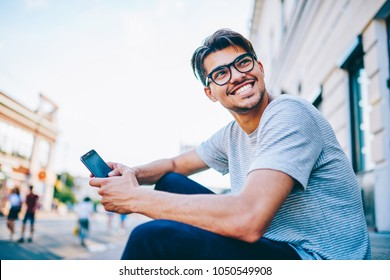 Happy young man in eye glasses laughing while holding smartphone in hand sitting outdoors in urban setting.Positive hipster blogger with mobile phone having fun on street in downtown