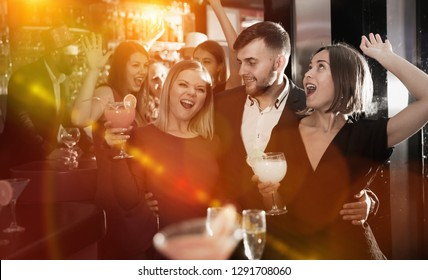 Happy young man with female friends enjoying cocktail party in bar
