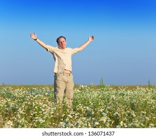 The happy young man  in the field of chamomiles