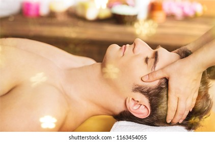 Happy young man getting facial massage on spa holiday