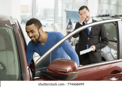 Happy young man getting inside a new car at the dealership professional salesman looking tired making facepalm gesture on the background copyspace fun expressive emotional crazy disgusted covering