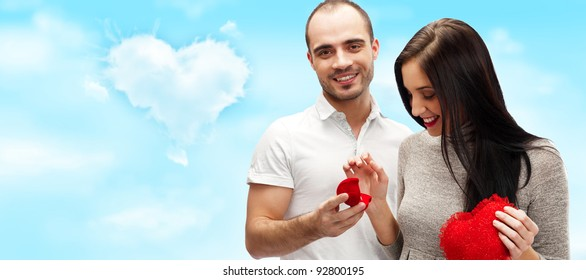 Happy young man gifting a ring to a beautiful surprised young woman on romantic background with sky and clouds of heart shape