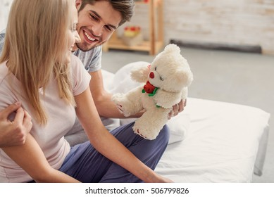 Happy young man is giving teddy bear to woman. He is embracing her and smiling. Couple is sitting on bed
