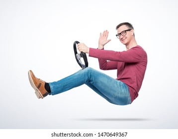 Happy young man in glasses driving a car sends greetings to the camera. Auto driver concept
