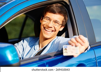 Happy young man in glasses showing his driving license from open car window