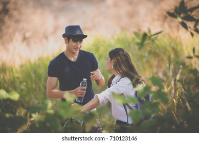 happy young man hand holding a bottle of drinking water talking with his girl friend  and looking each other with enjoying on vacations at the park.