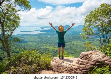 Happy young man with hands raised up stands on rock high in mountains and watches landscape of forest, hills, and sea. Concept of success, healthy lifestyle, harmony with nature & travel in vacation.