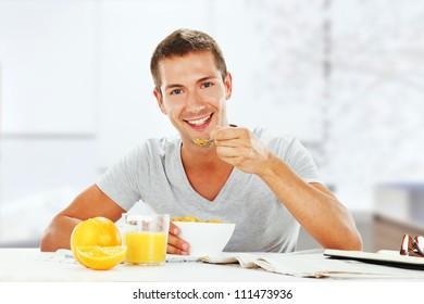 happy young man having energetic breakfast