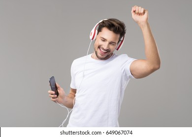 Happy young man with headphones. Listening music