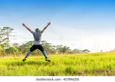 Happy young man hiker jumping on a green field.