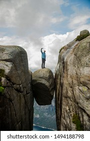 happy young man hiking taking selfie standing on Kjeragbolten raised hands Traveling in Norway Kjerag mountains summer vacations adventure success concept